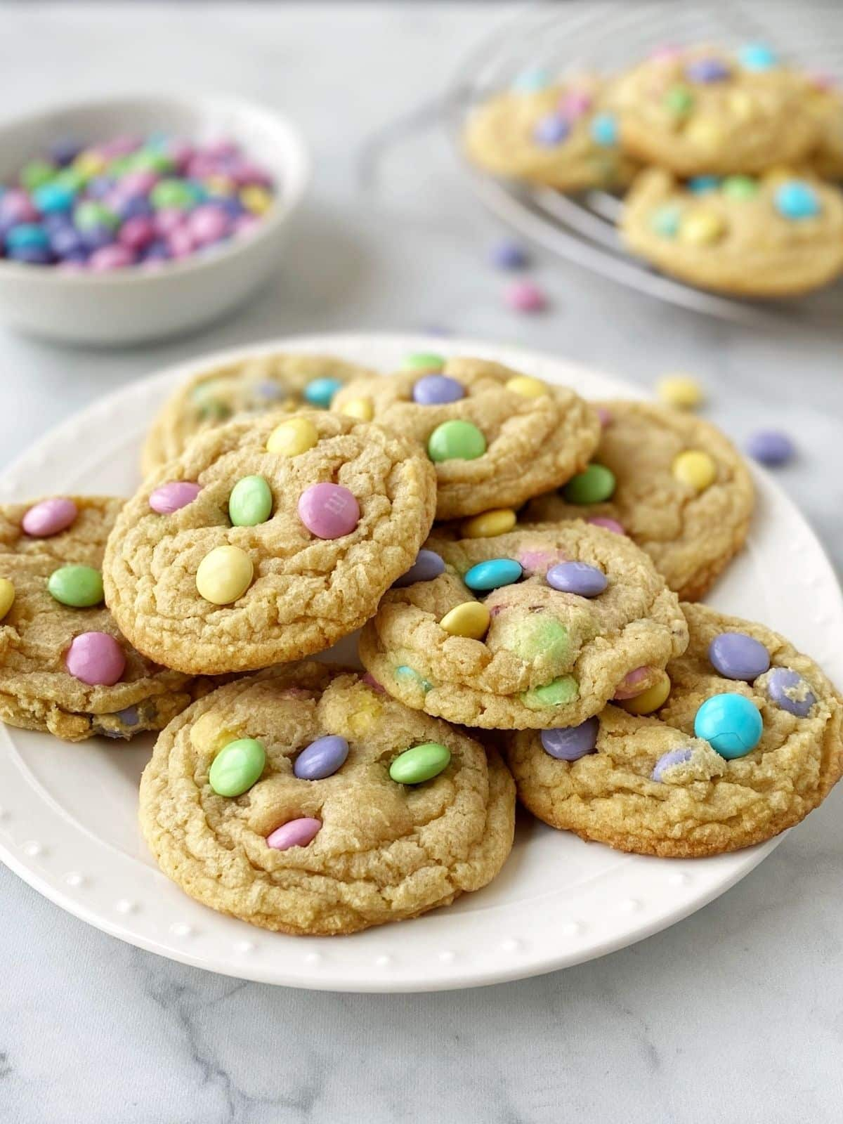 side view of cookies on a plate with a dish of candies and more cookies in the background