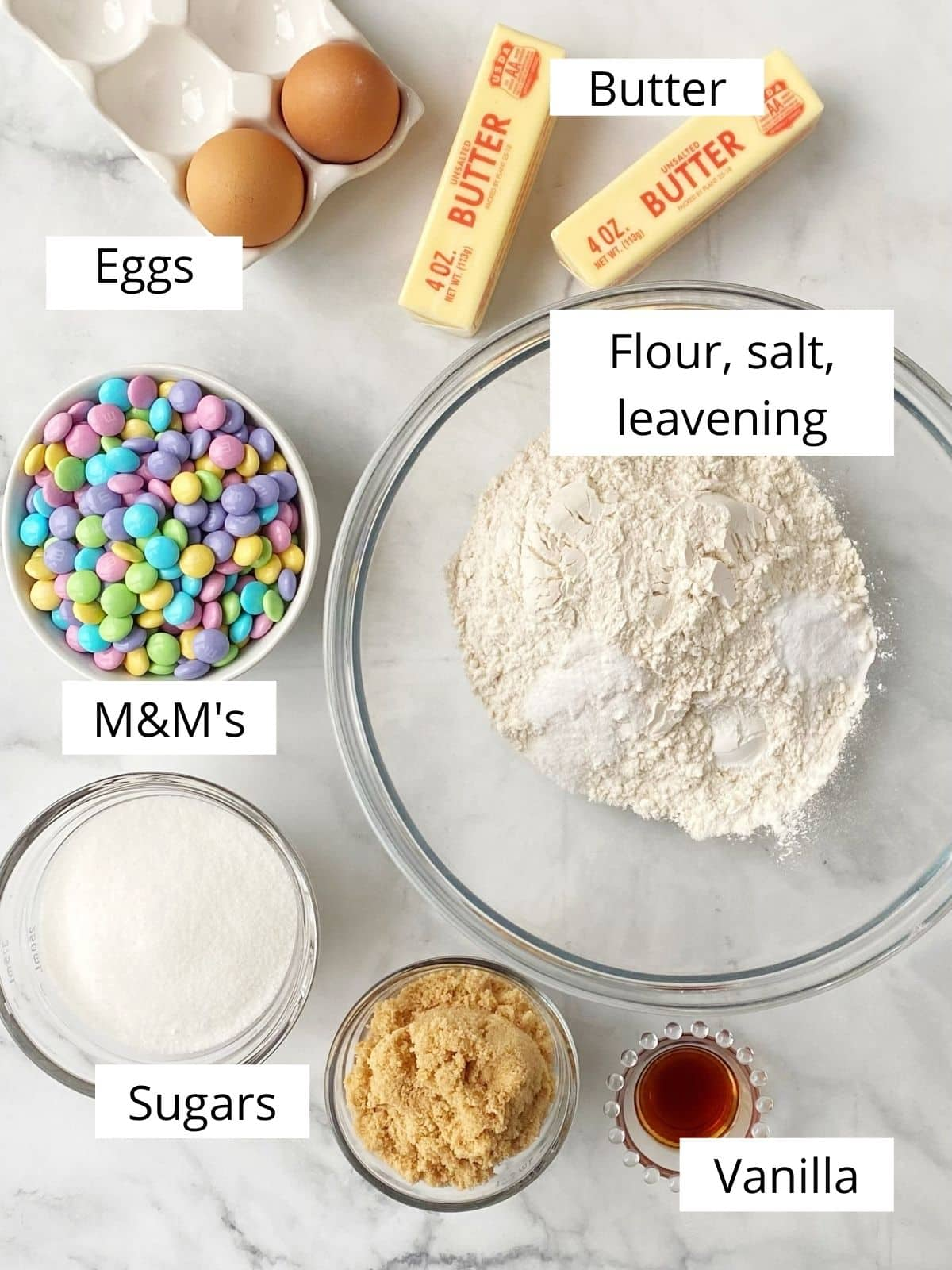 array of ingredients - eggs, butter, flour, sugars, salt, vanilla, leavening, chocolate candies