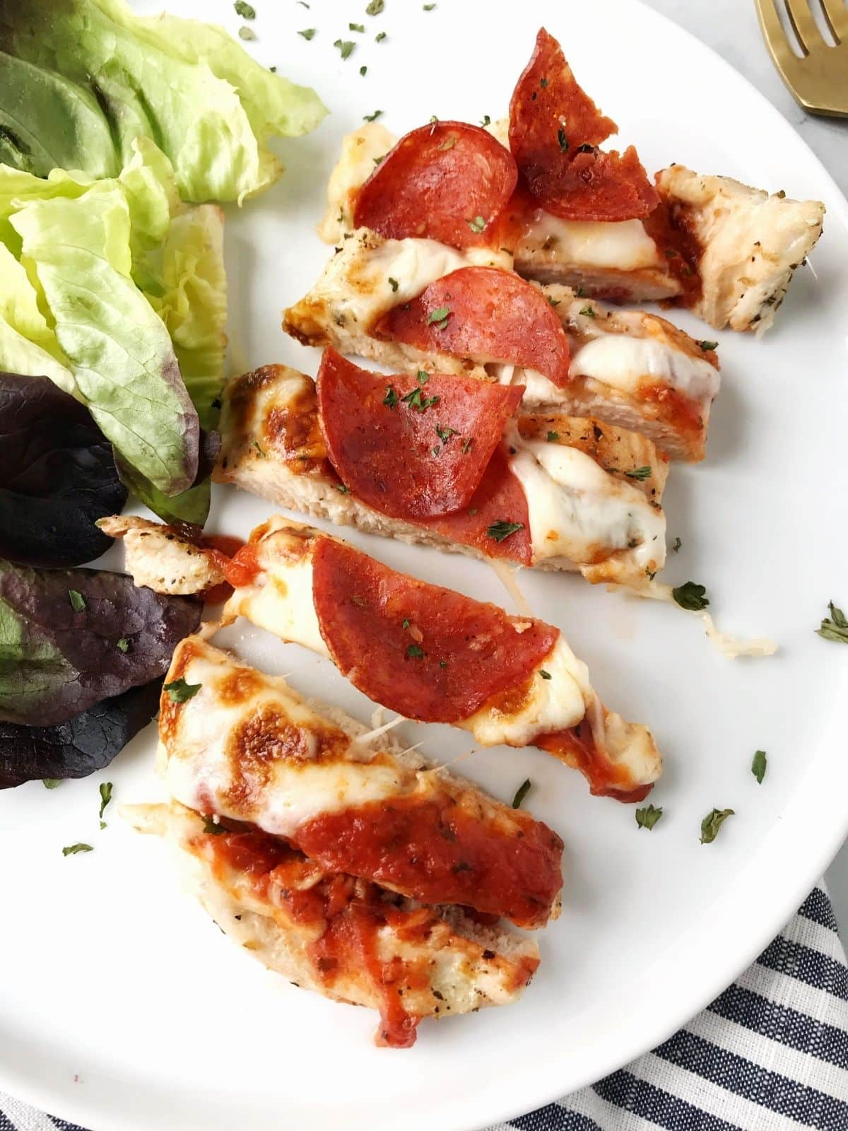 sliced chicken on a plate with a green salad