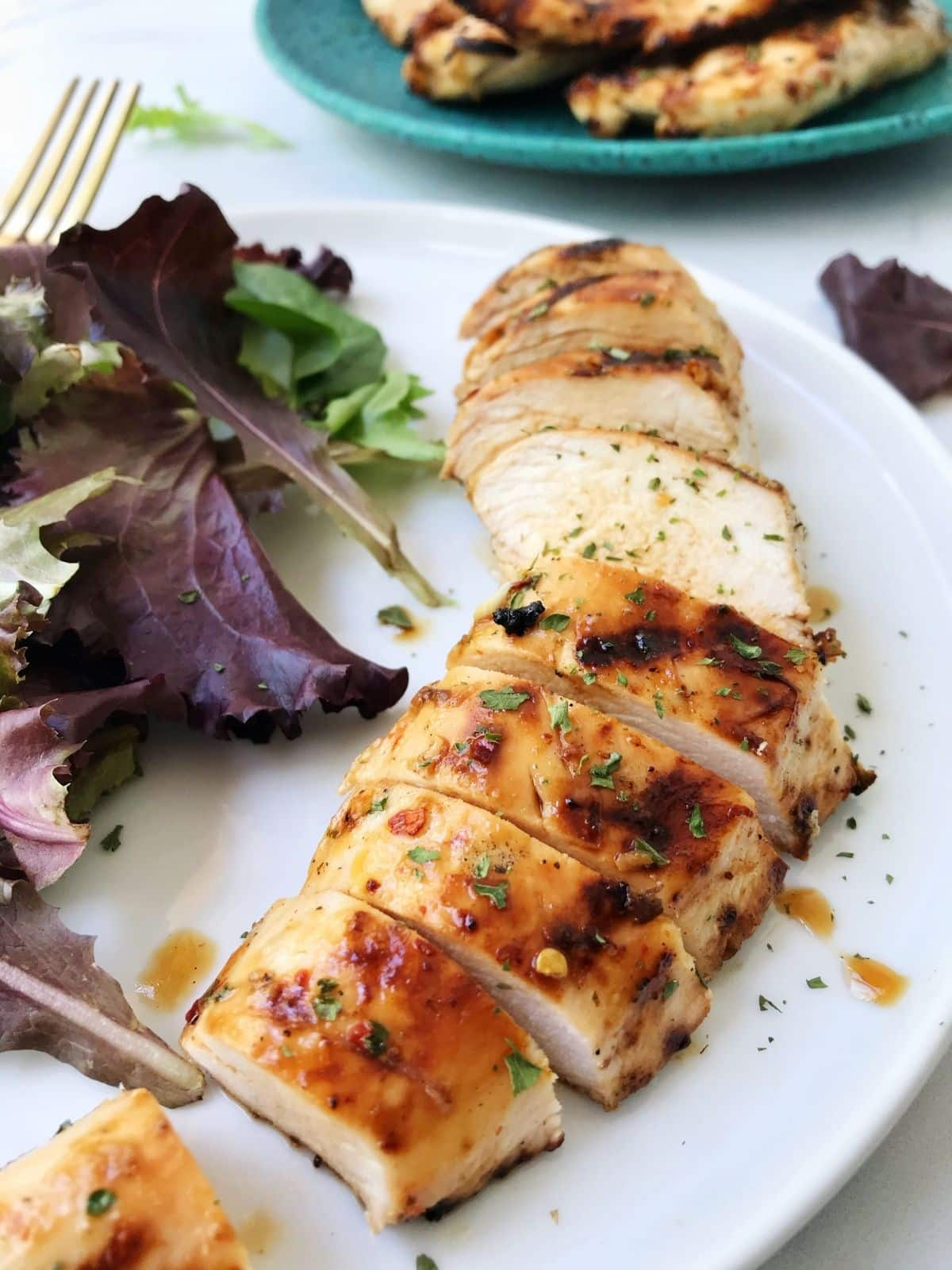 sliced chicken on a plate with salad greens