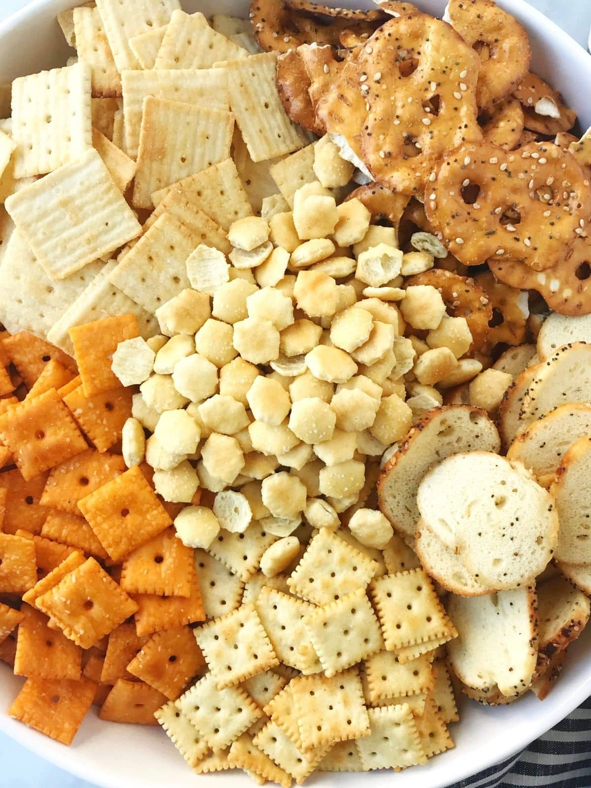 snack mix ingredients grouped together in bowl before mixing
