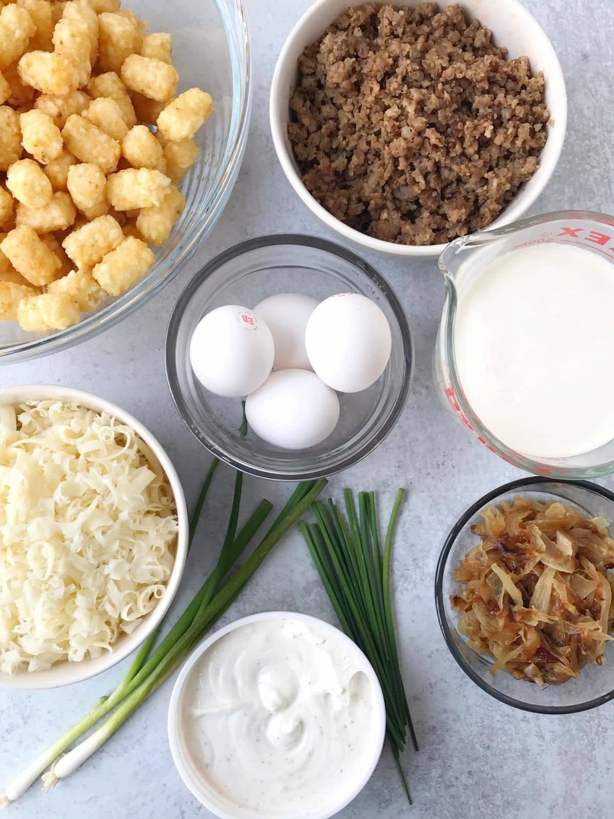 array of ingredients - tater tots, sausage, onions, eggs, cheese, cream, dip, chives, and scallions
