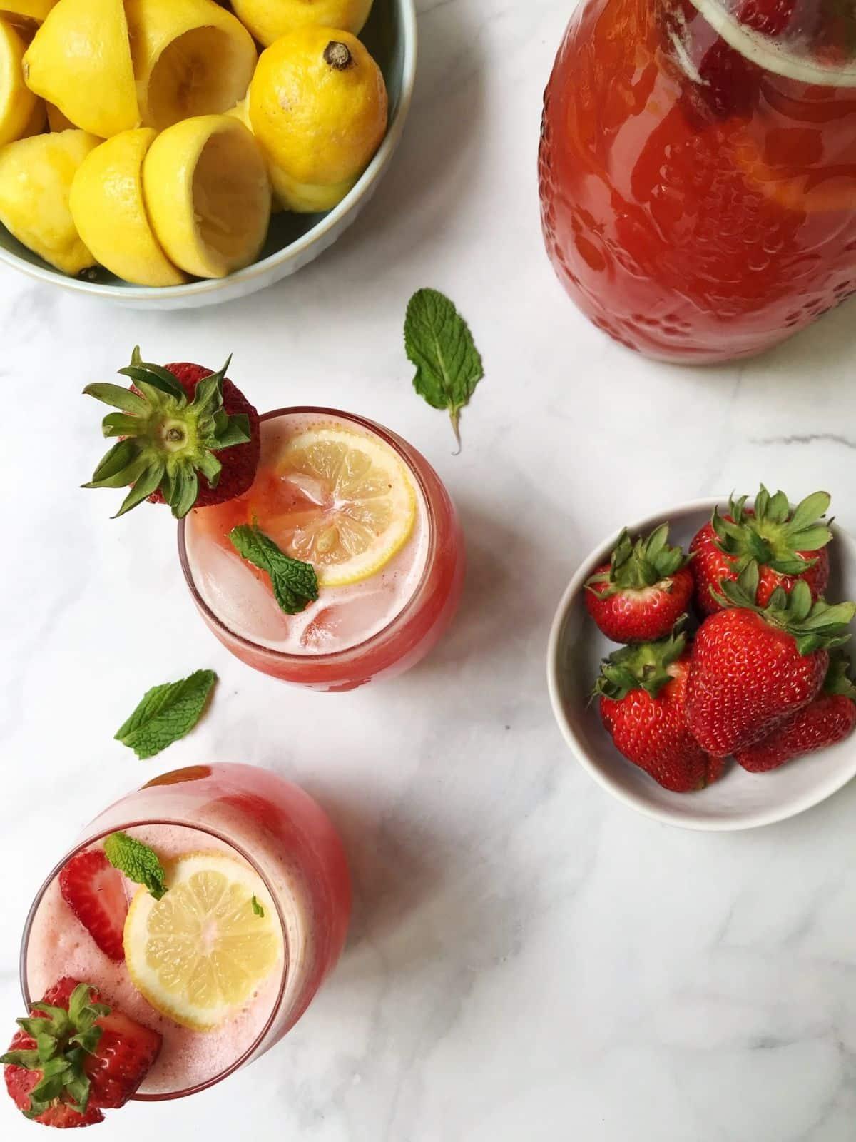 pitcher of lemonade, glasses, and lemons and strawberries