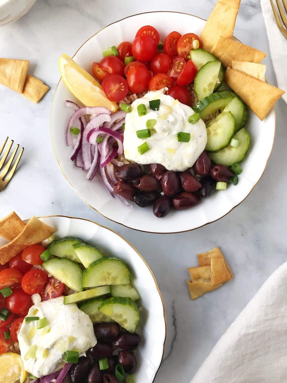two rice bowls with garnishes and pita chips