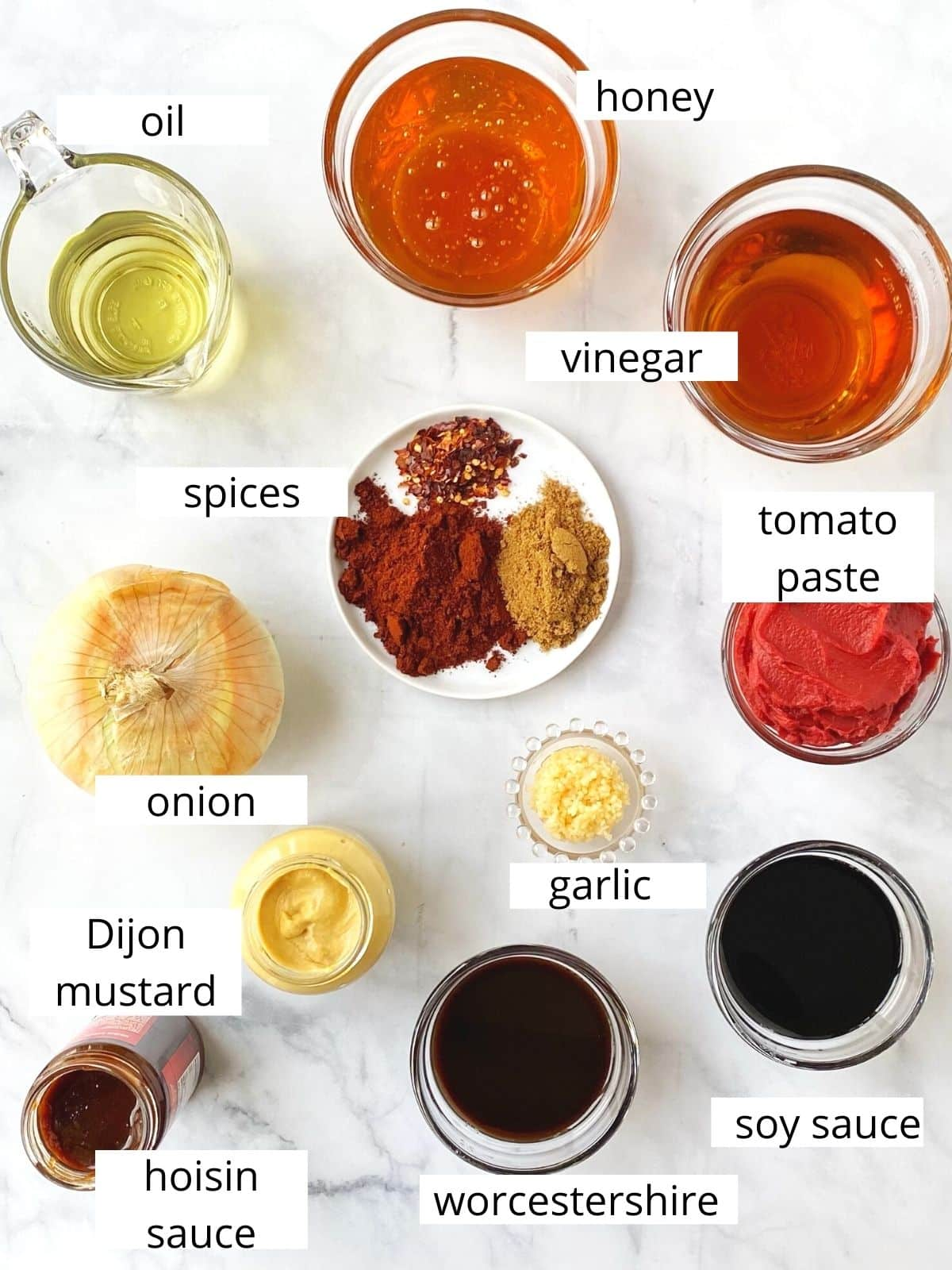 array of ingredients - vinegar, honey, soy, worcestershire, tomato paste, spices, hoisin, mustard, onion, garlic, and oil