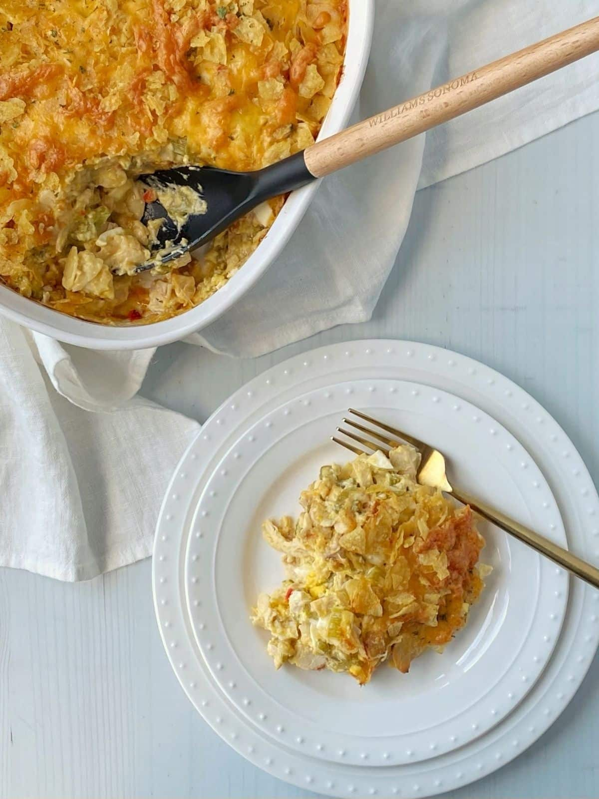 serving of casserole on a white plate next to the casserole dish