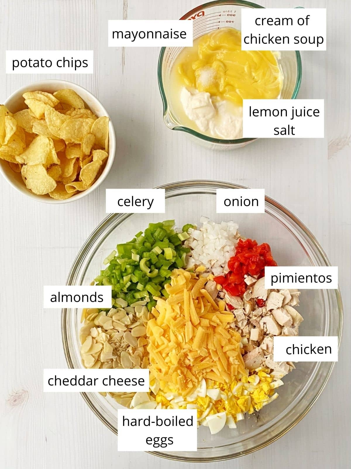 array of ingredients - mayo, cream of chicken soup, lemon juice, potato chips, onions, celery, pimientos, chicken, cheese, hard-boiled eggs, almonds