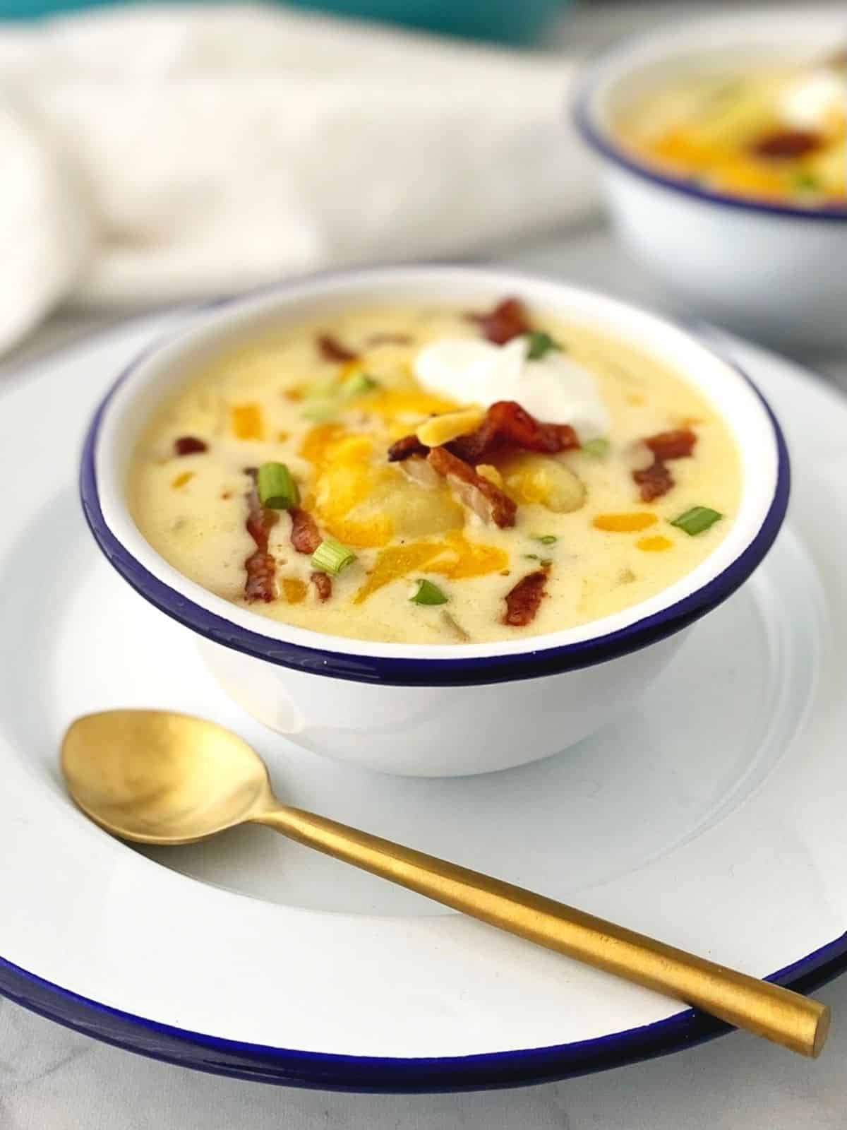 bowl of soup on a white plate with spoon