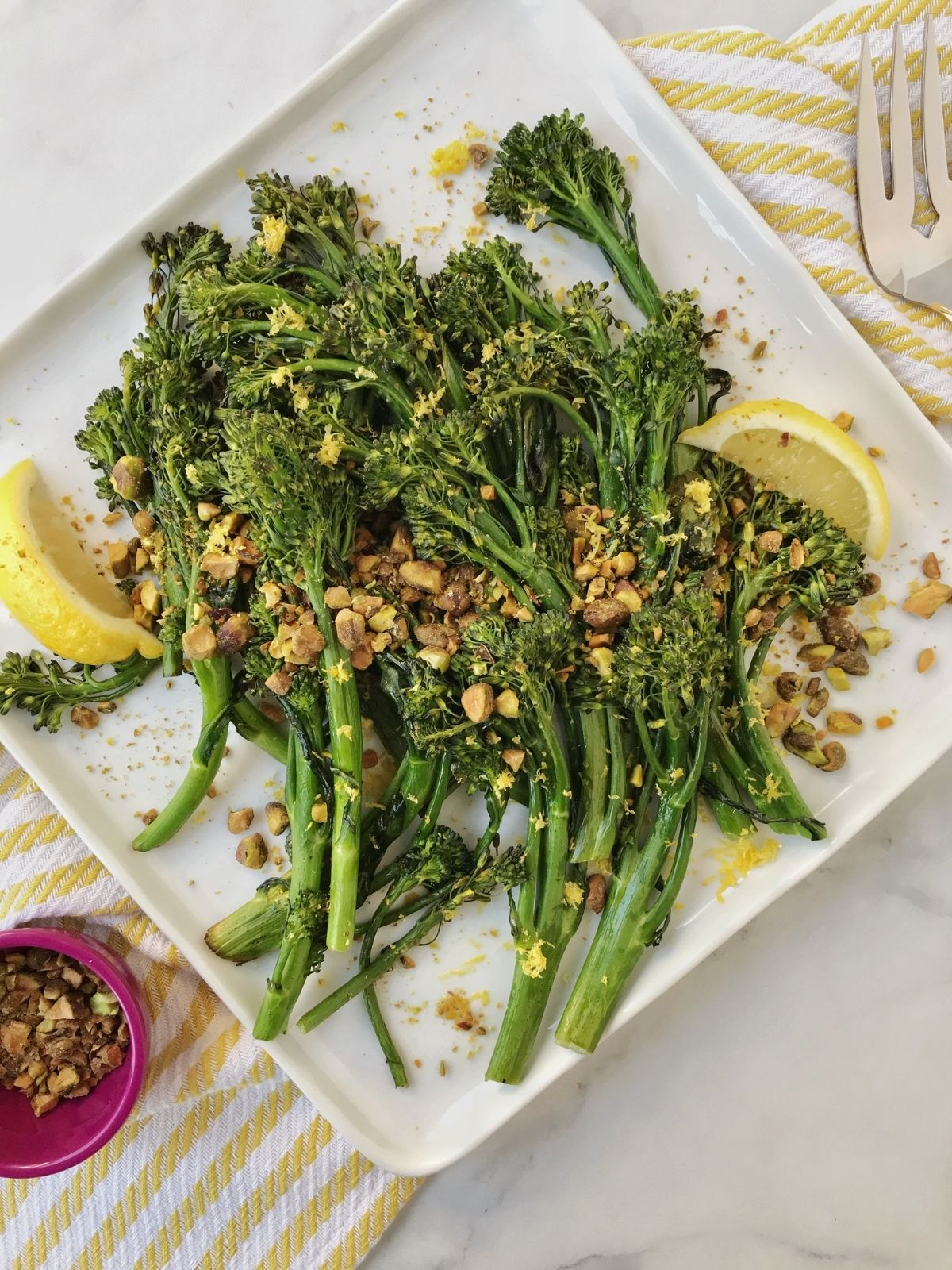 platter of broccolini garnished with nuts and lemon