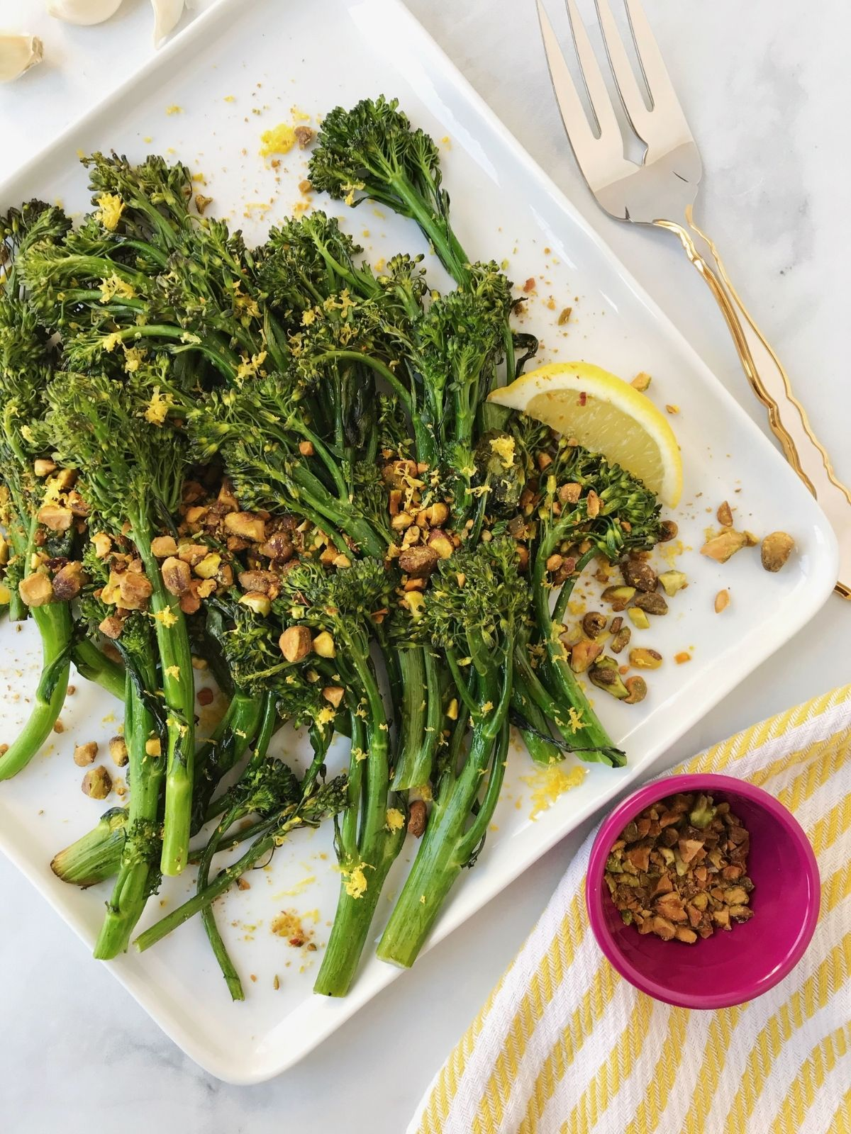 fork alongside a plate of broccolini