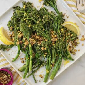 plate of broccolini with lemon wedges