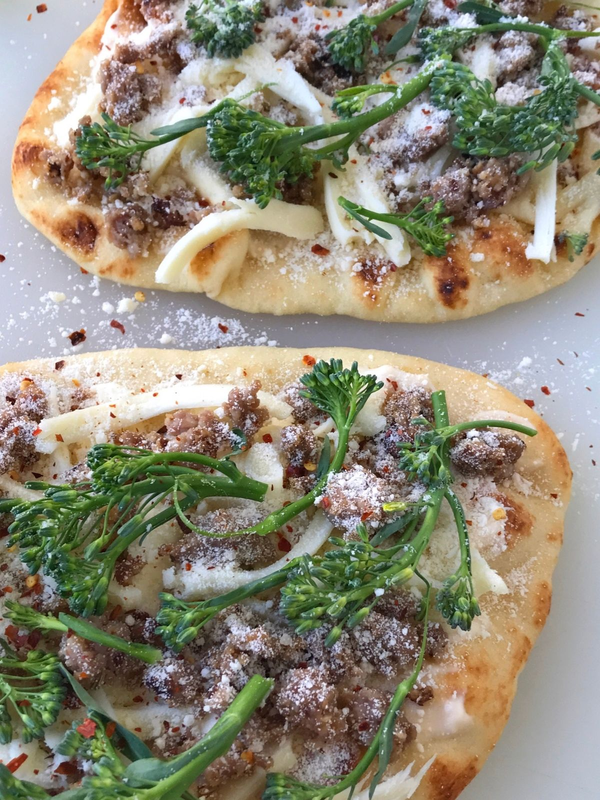 naan bread topped with sausage and broccolini
