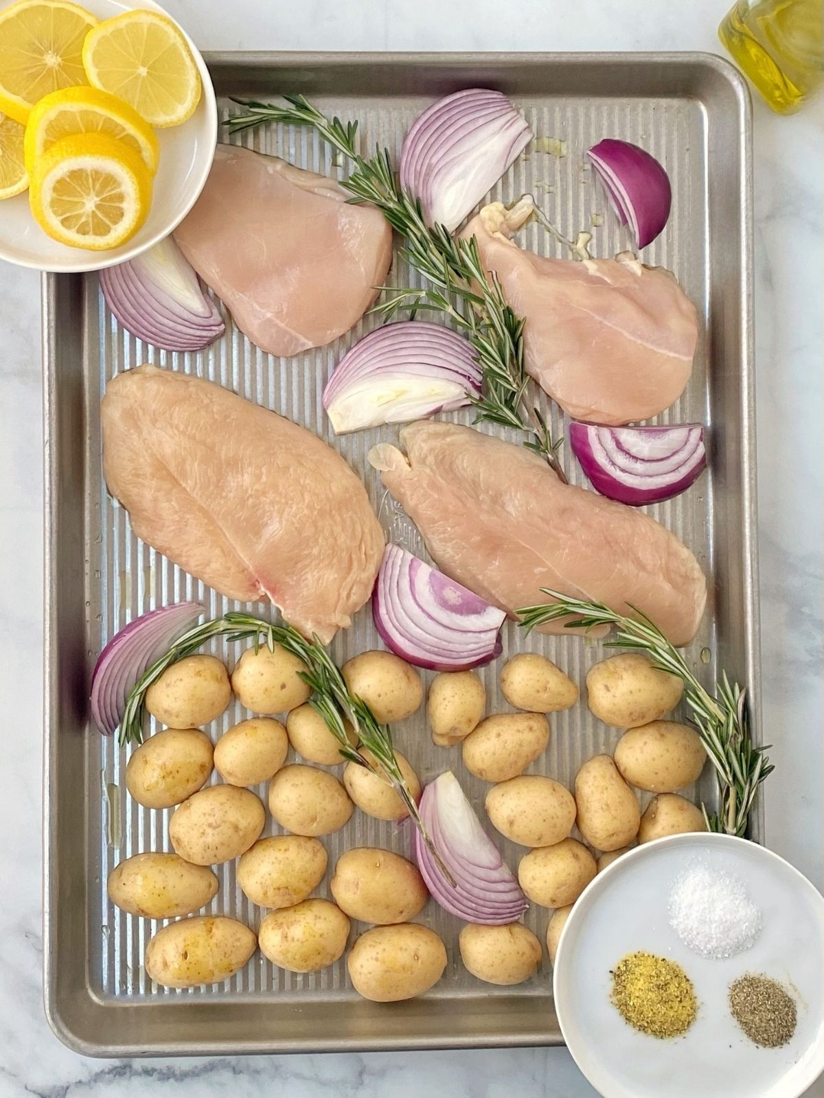 sheet pan of ingredients - chicken, potatoes, onions, rosemary, lemon slices, seasonings