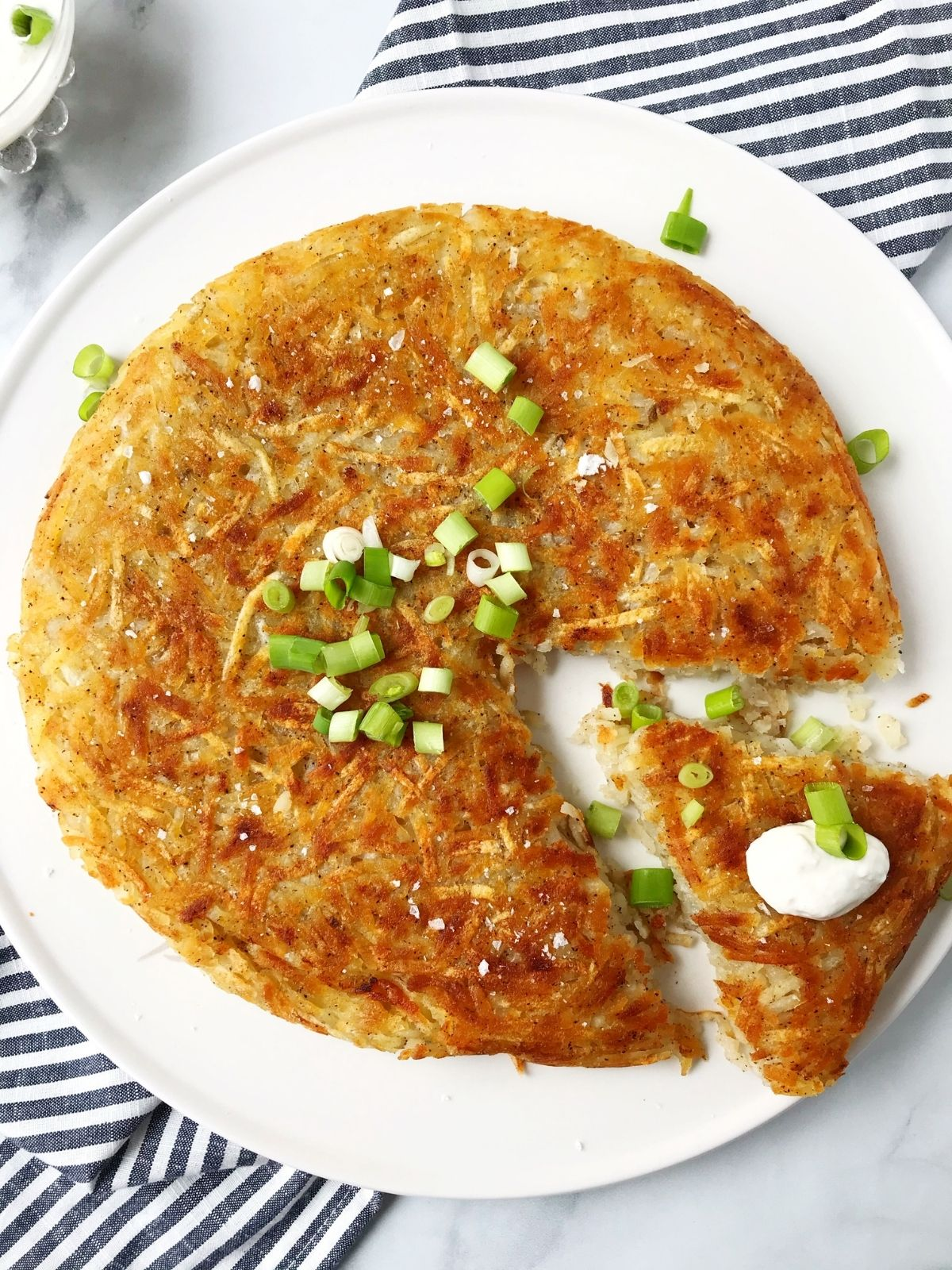 overhead shop of hash brown garnished with sour cream and scallions