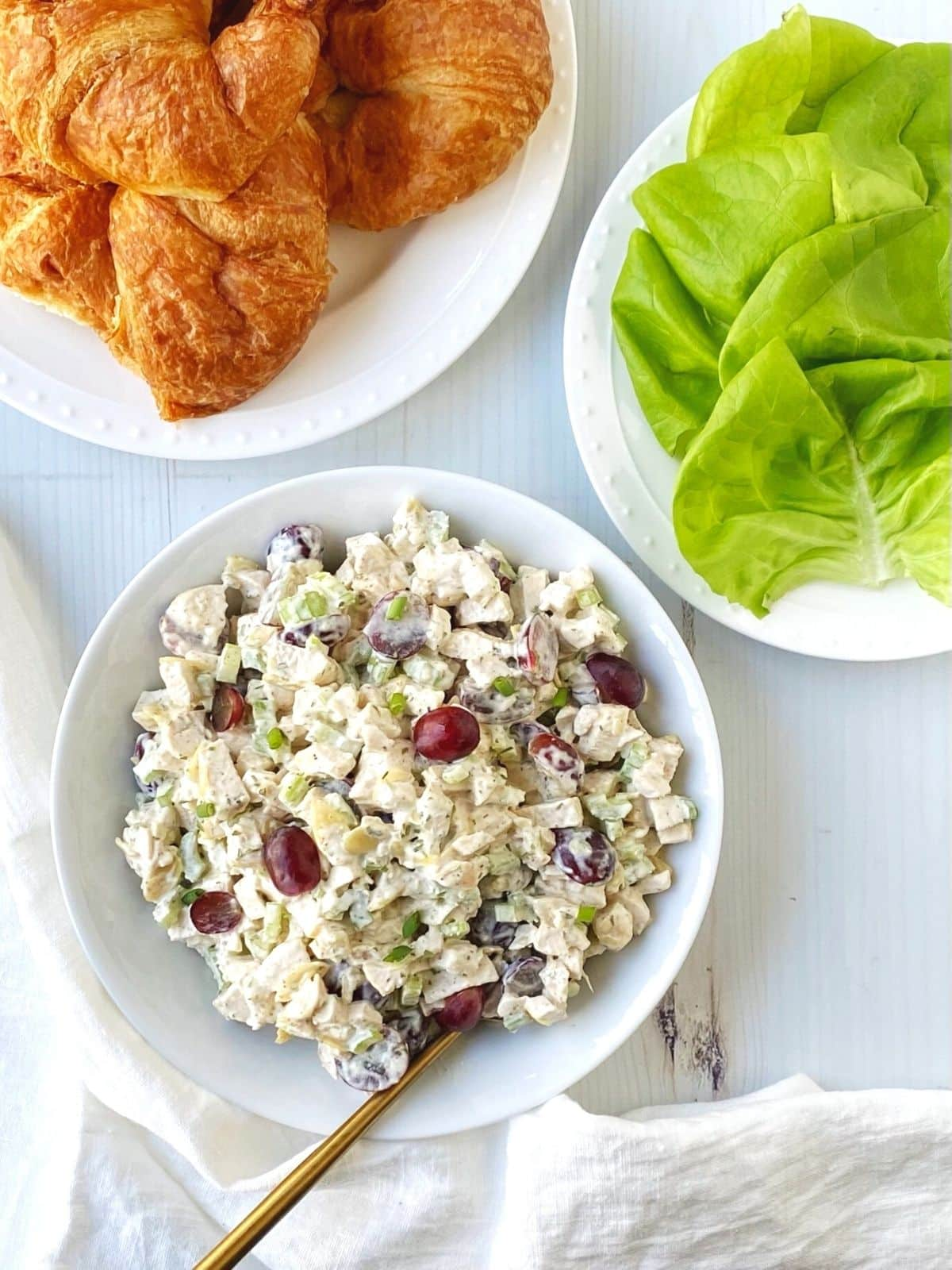 bowl of chicken salad with a plate of croissants and lettuce for building sandwiches