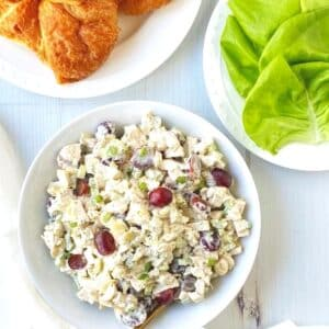 white bowl of chicken salad with croissants and lettuce ready to build sandwiches