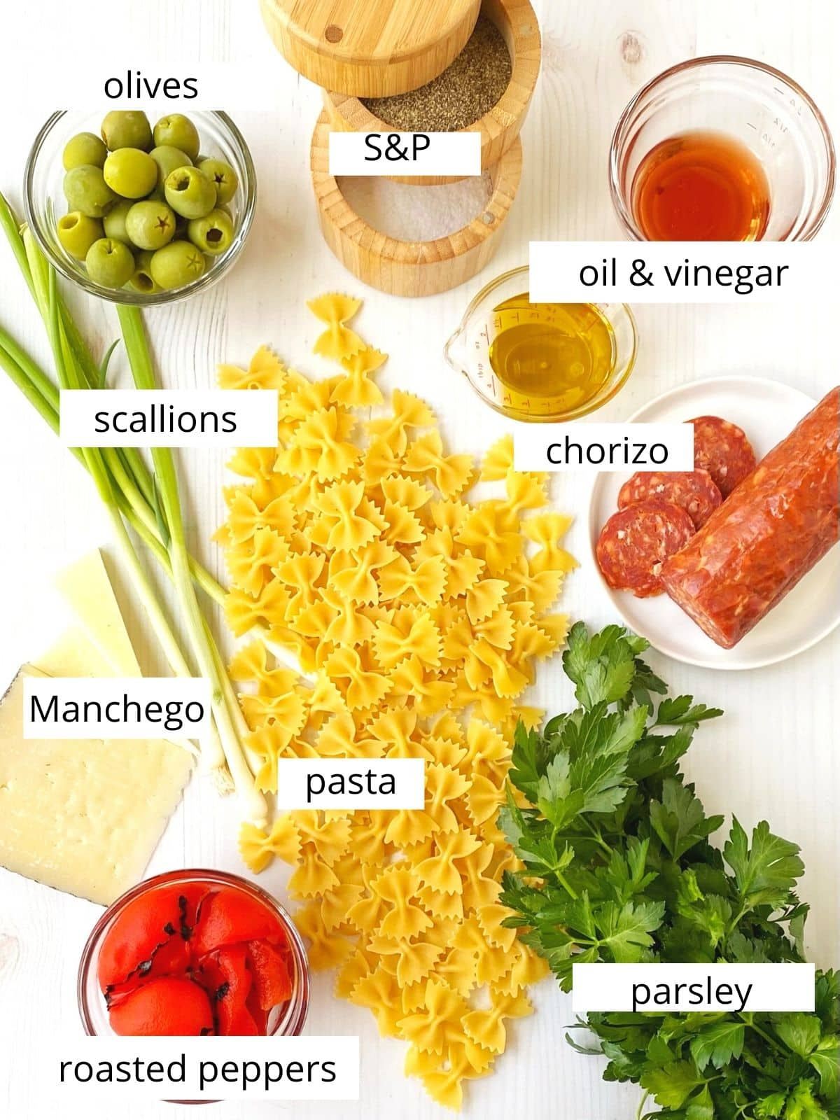 array of ingredients - pasta, chorizo, cheese, olives, parsley, peppers, scallions, oil, and vinegar