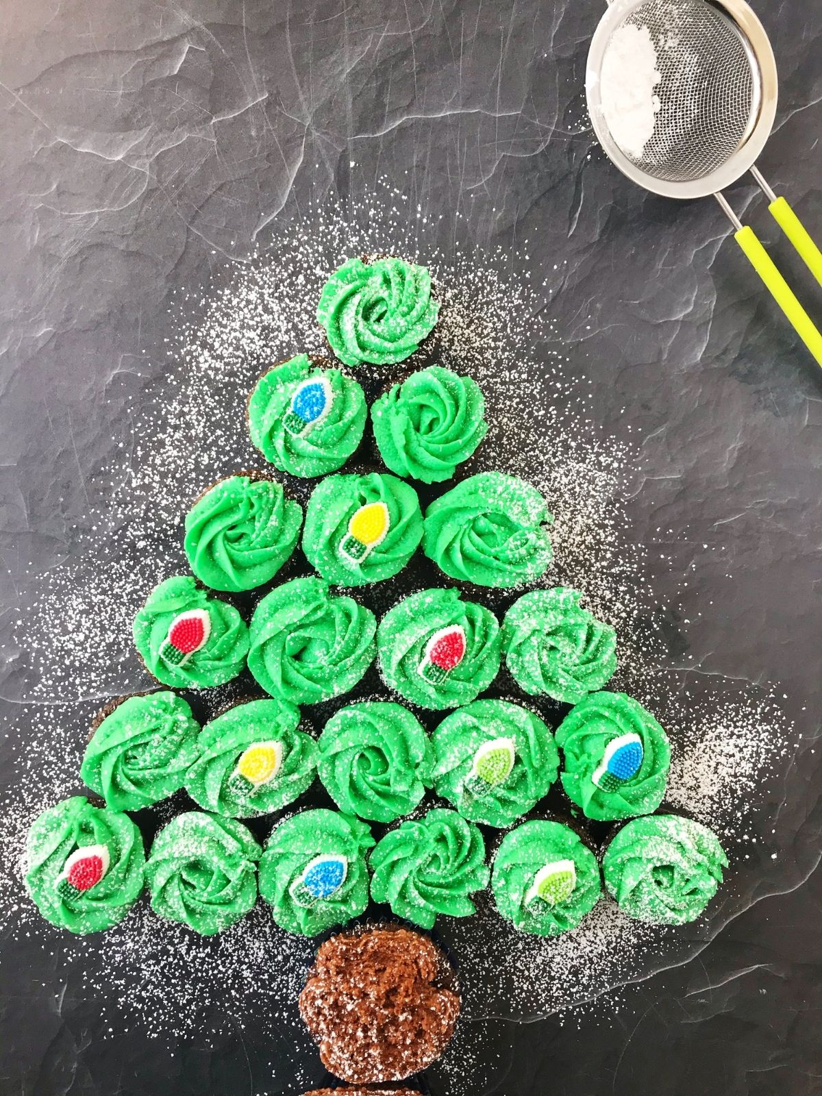 cupcakes arranged in the shape of a tree with powdered sugar dusted over the top