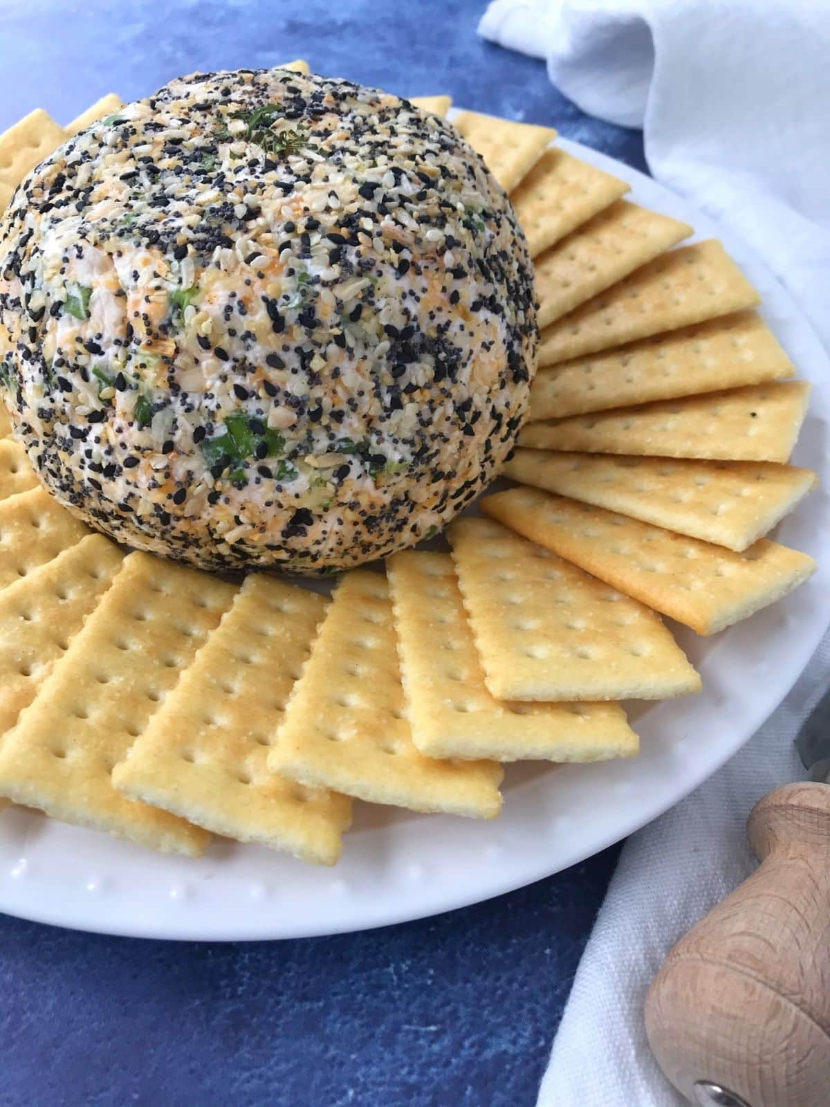 cheese ball on a white plate surrounded by crackers