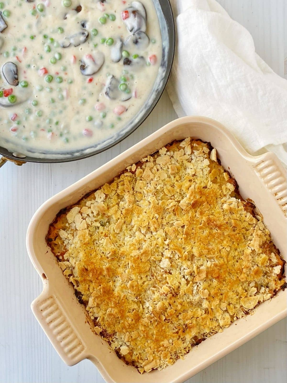 salmon loaf in baking dish next to skillet of cream sauce