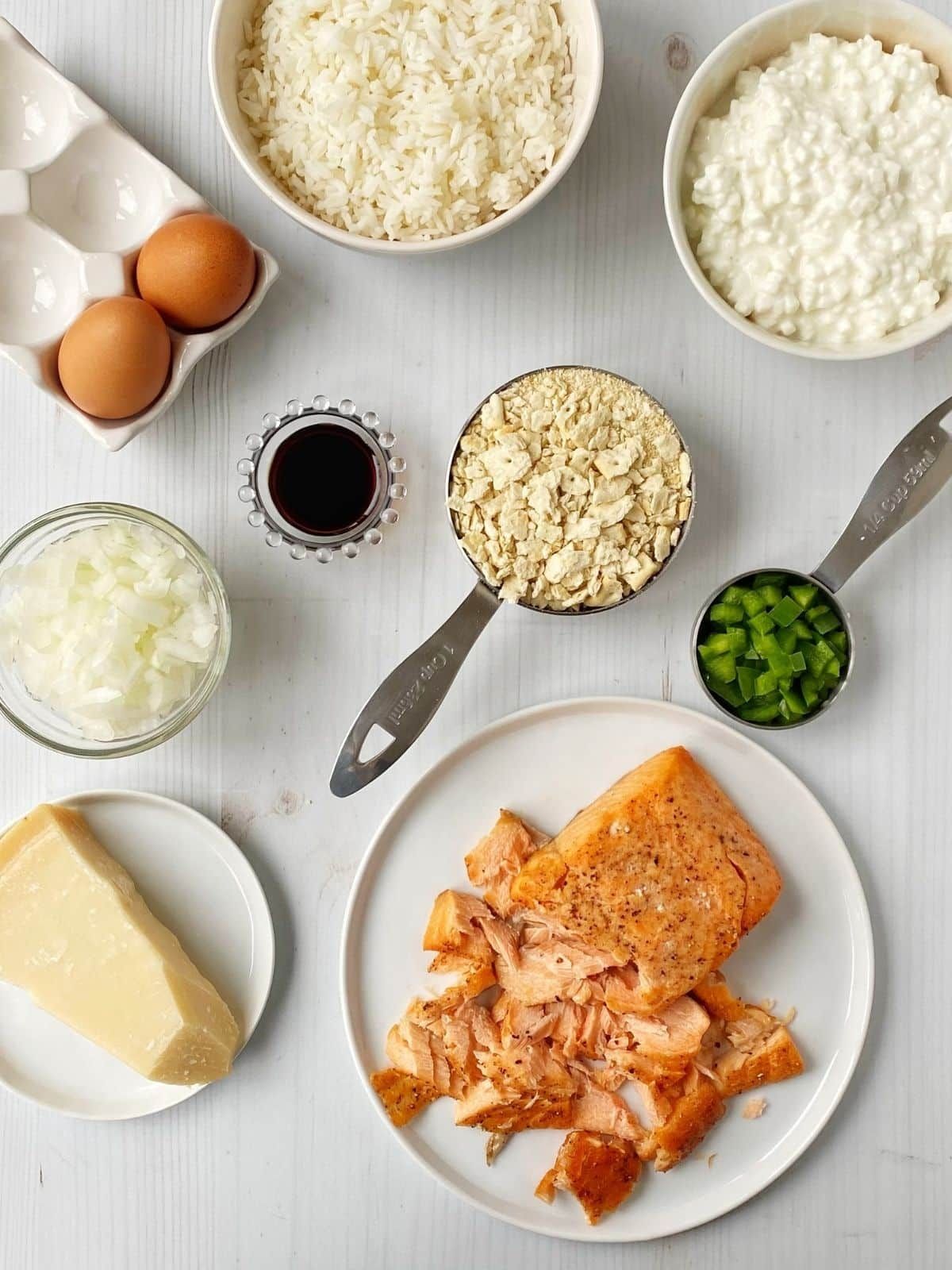 array of salmon loaf ingredients - salmon, rice, cottage cheese, onion, green peppers, soy sauce, eggs, cracker crumbs and cheese