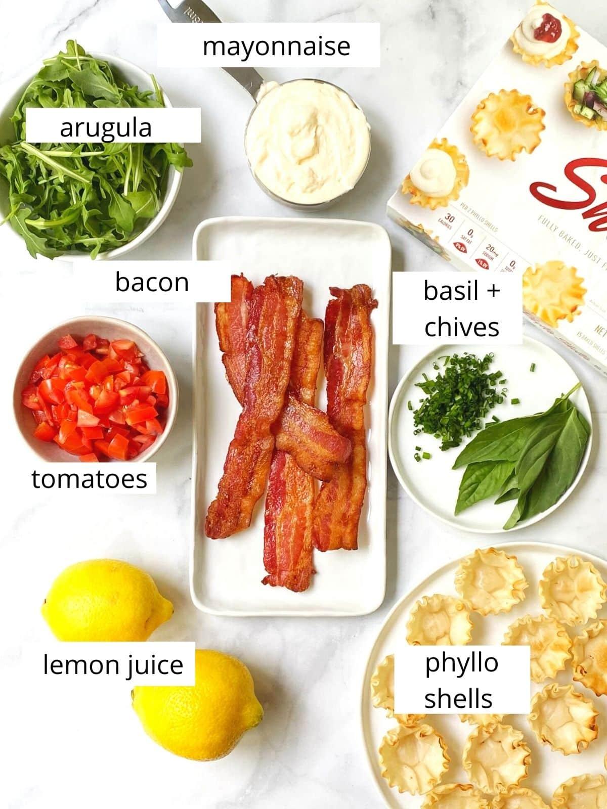 array of ingredients - arugula, mayo, herbs, bacon, tomatoes, lemon, and phyllo shells