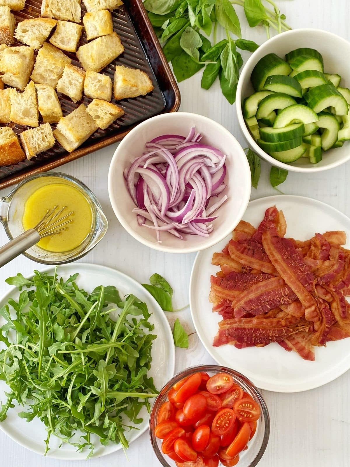 array of ingredients - bread, cucumbers, onions, bacon, tomatoes, arugula, vinaigrette