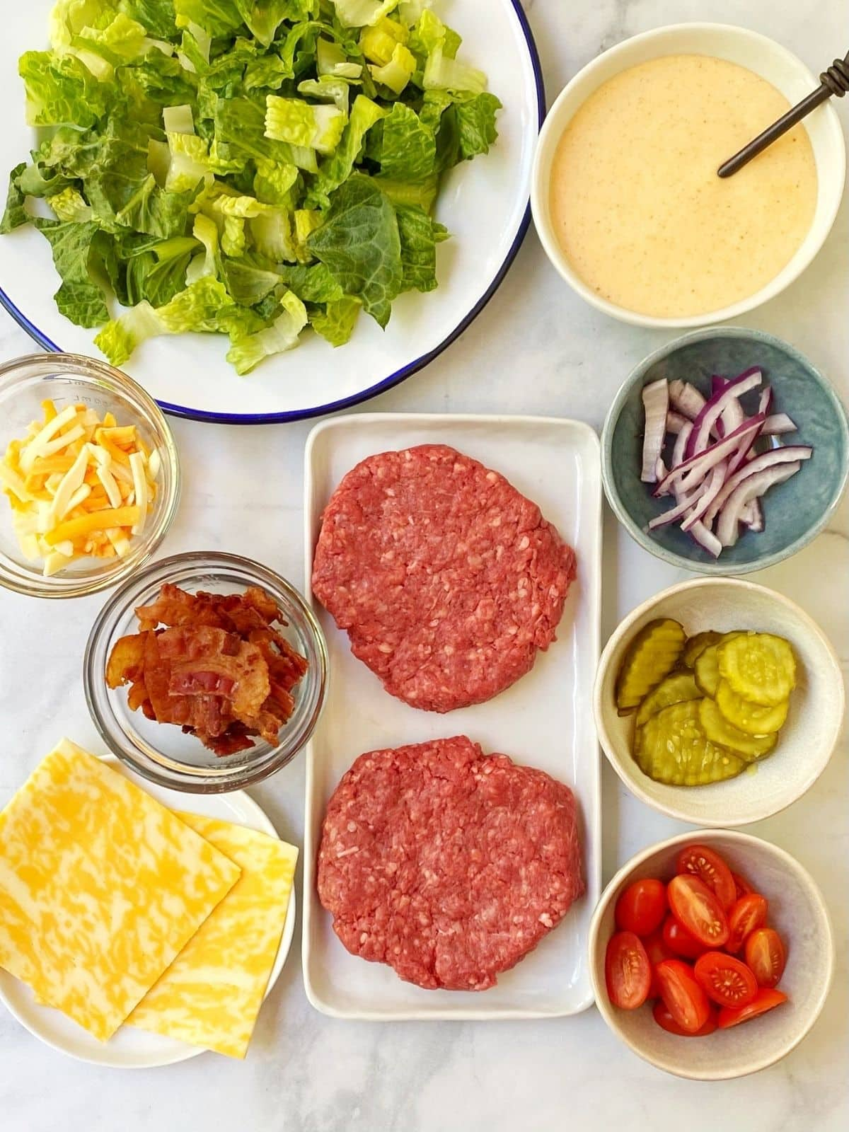 array of ingredients - beef, lettuce and salad toppings, burger sauce dressing