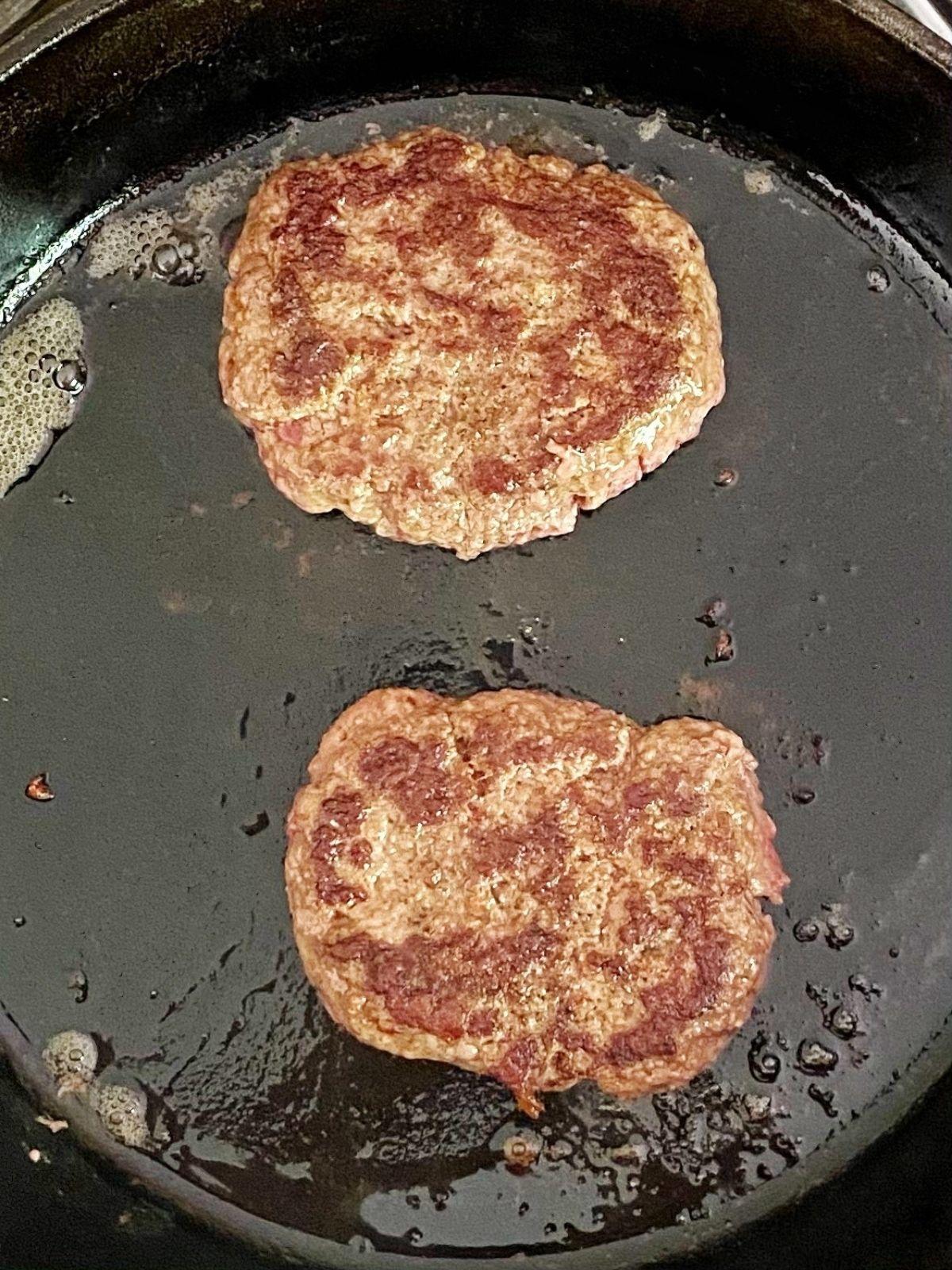 burgers cooking in skillet