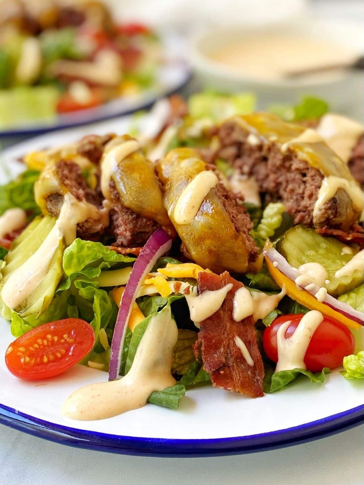 close up of cheeseburger salad on a white plate