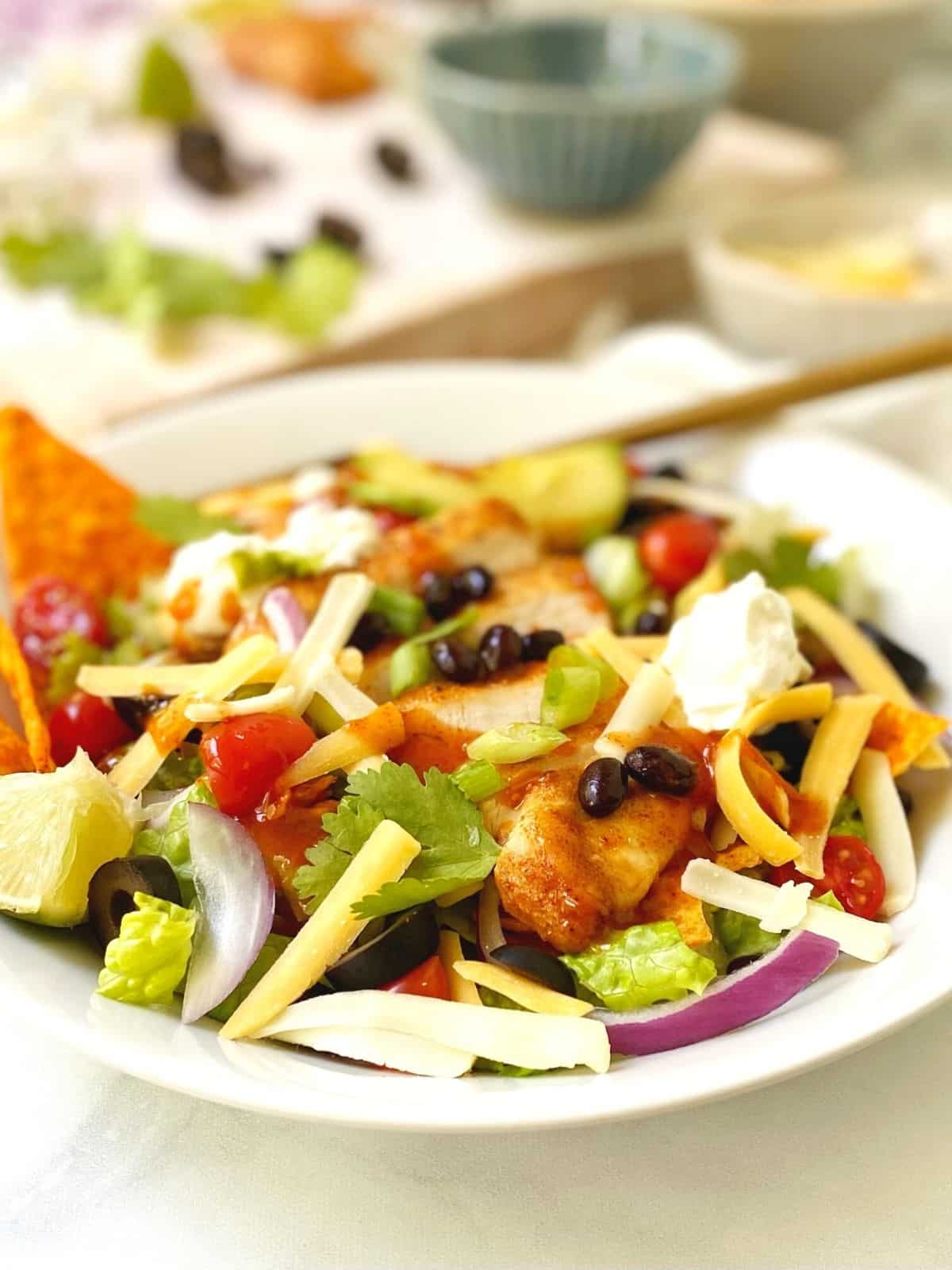 salad in white bowl with fork next to board of toppings