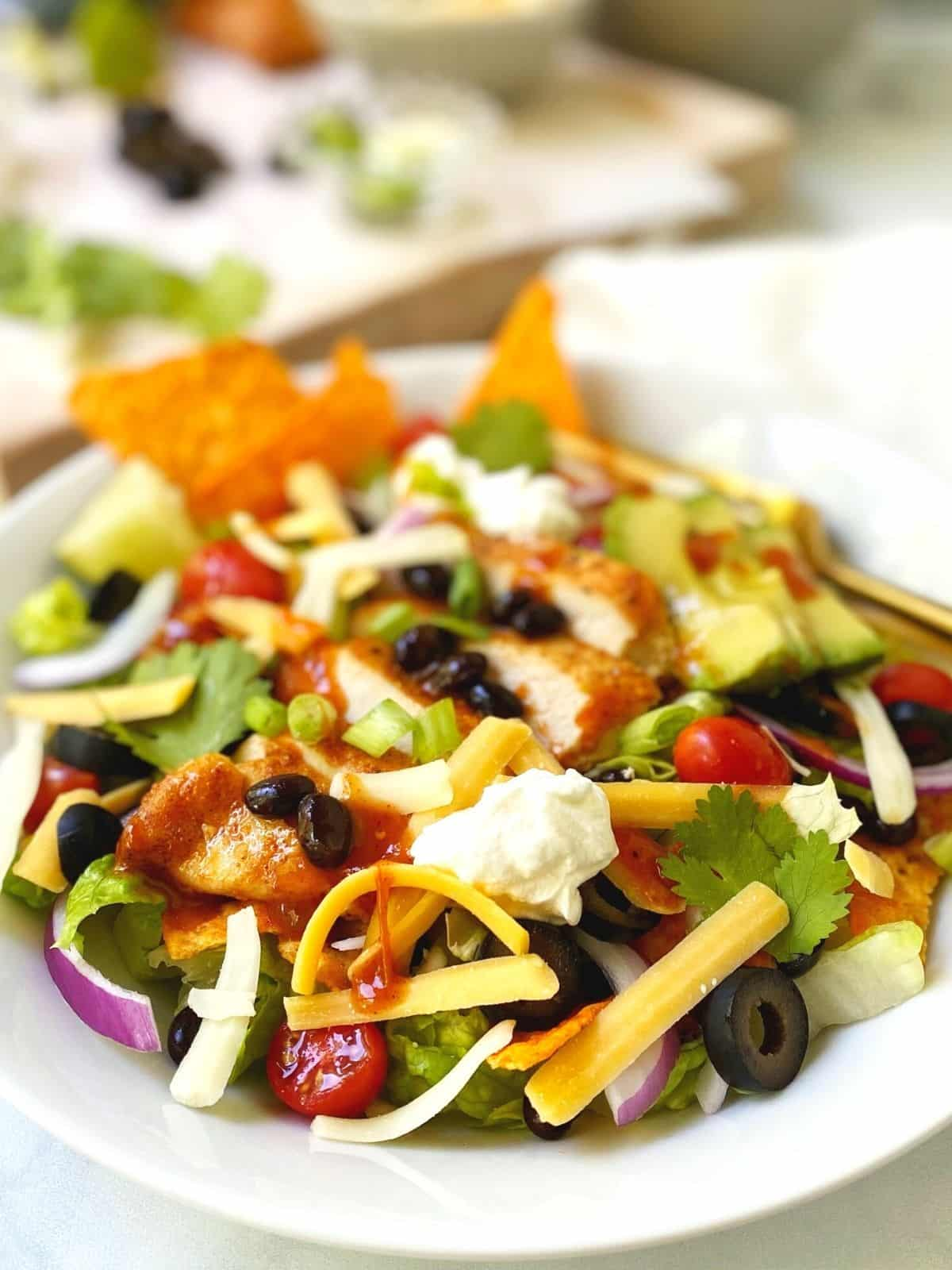 white bowl of salad with board of toppings in the background