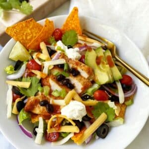 taco salad in white bowl with a fork