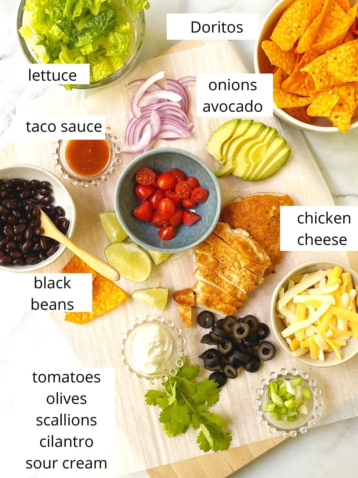 array of ingredients - lettuce, chips, chicken, cheese, and various taco salad fixings
