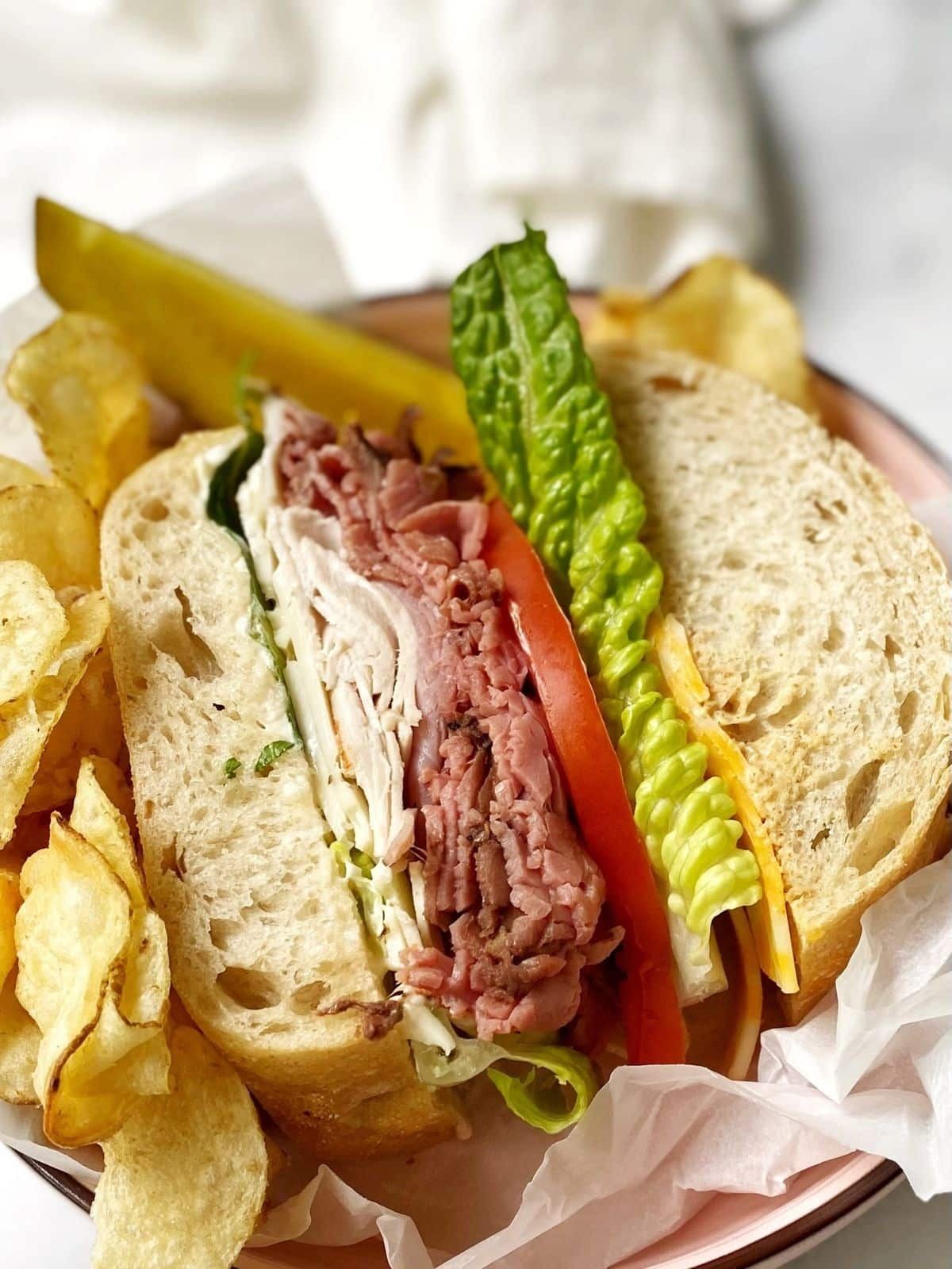 sandwich in a dish with chips and pickle