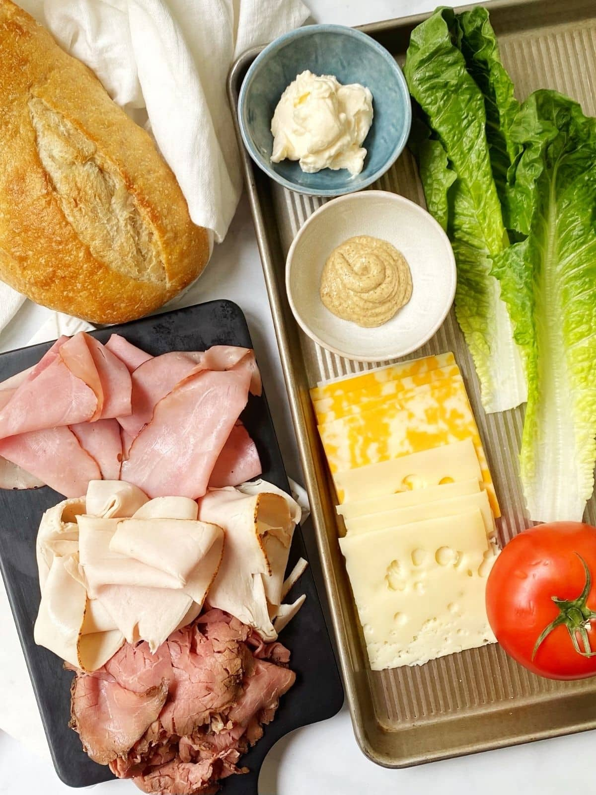 array of ingredients - bread, meat, cheese, lettuce, tomatoes, mayo and mustard