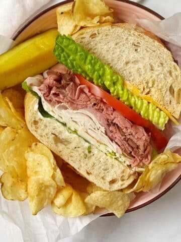overhead shot of a wedge of sandwich served with chips and a pickle
