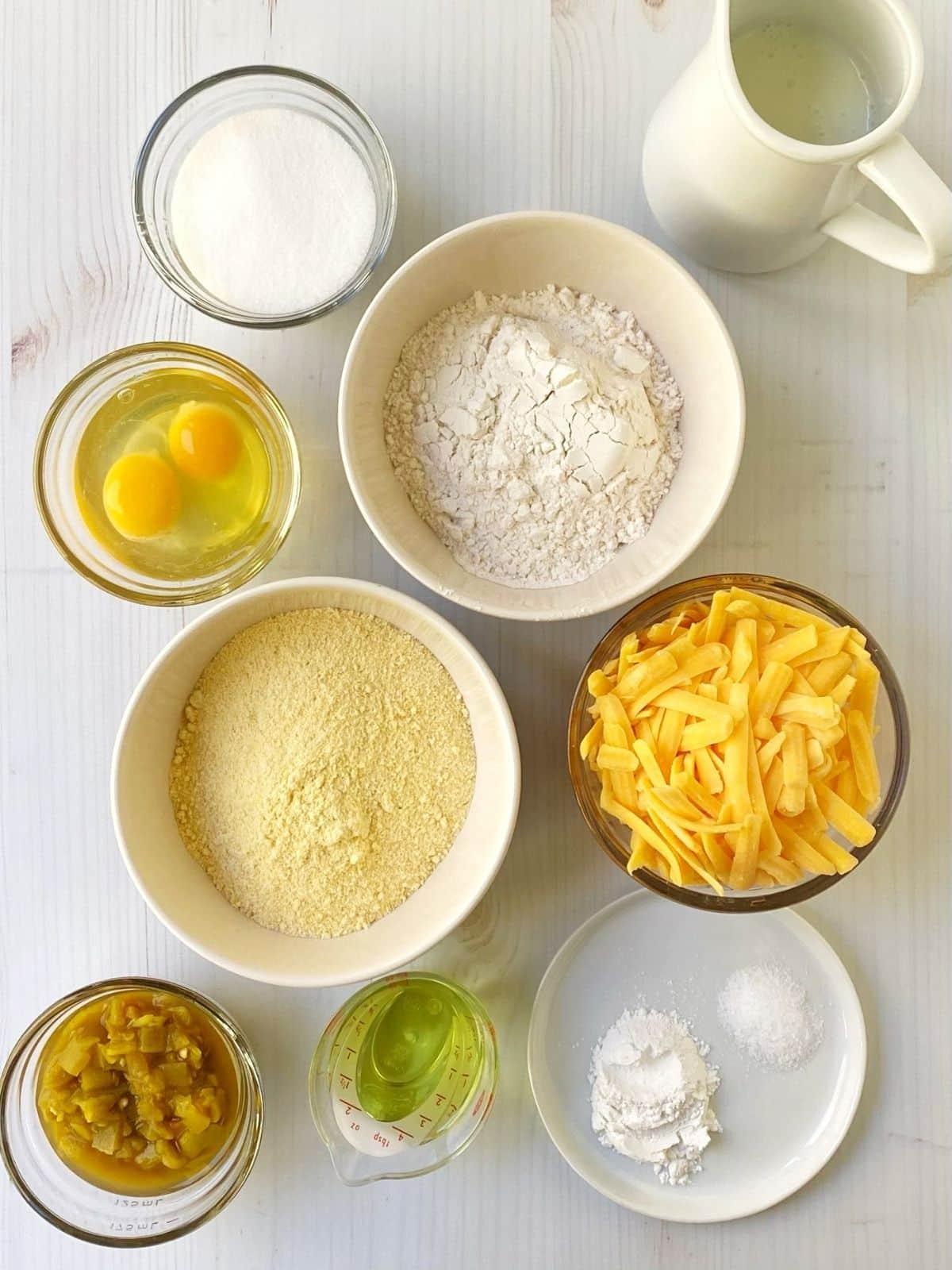 array of ingredients - flour, cornmeal, sugar, baking powder, salt, buttermilk, oil, eggs, cheese, chiles