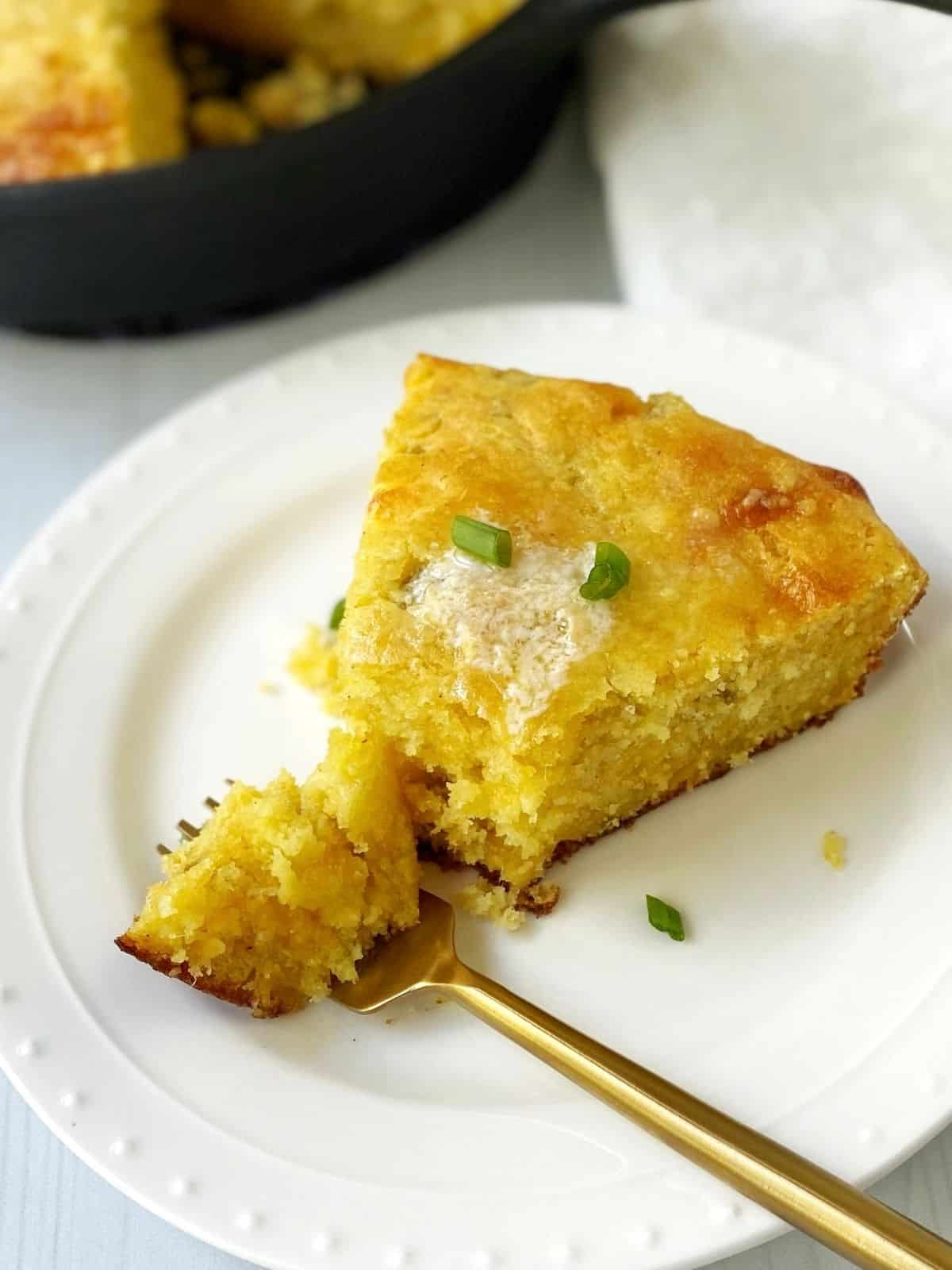 fork in a slice of cornbread on a white plate