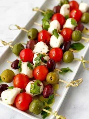 platter of mozzarella, tomato, and olive skewers