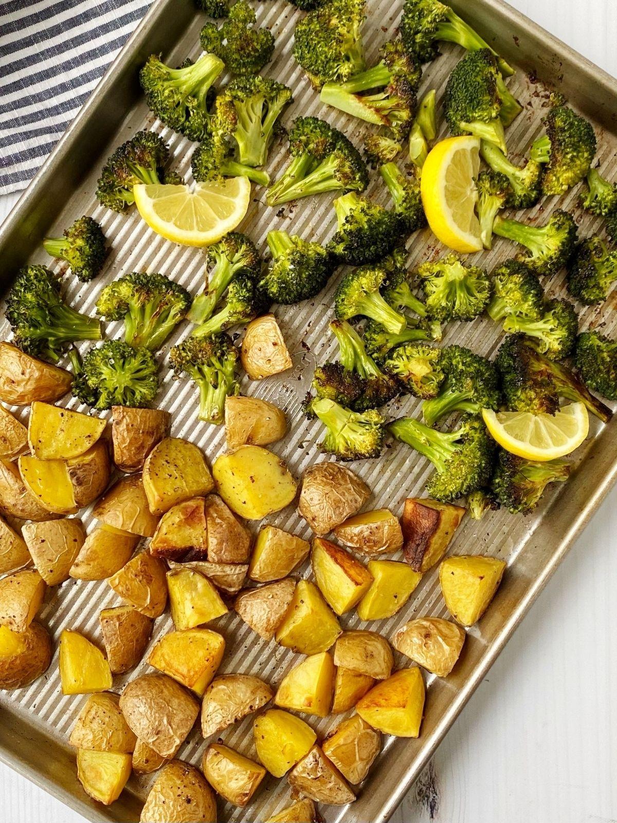 pan of roasted veggies with lemon wedges
