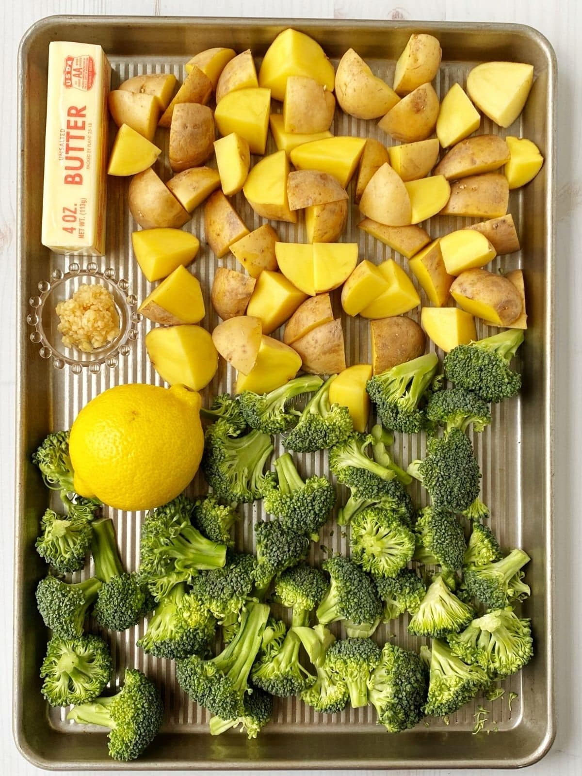 sheet pan with ingredients for roasted veggies including butter, garlic, and lemon