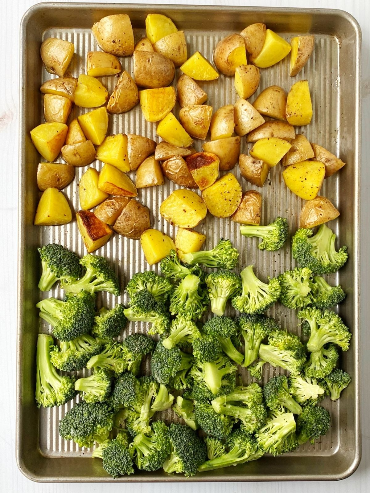 broccoli added to sheet pan with partially roasted potatoes