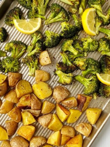 pan of roasted potatoes and broccoli garnished with lemon