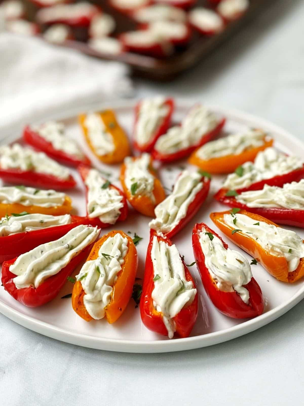 white plate of stuffed peppers with baking sheet in the background