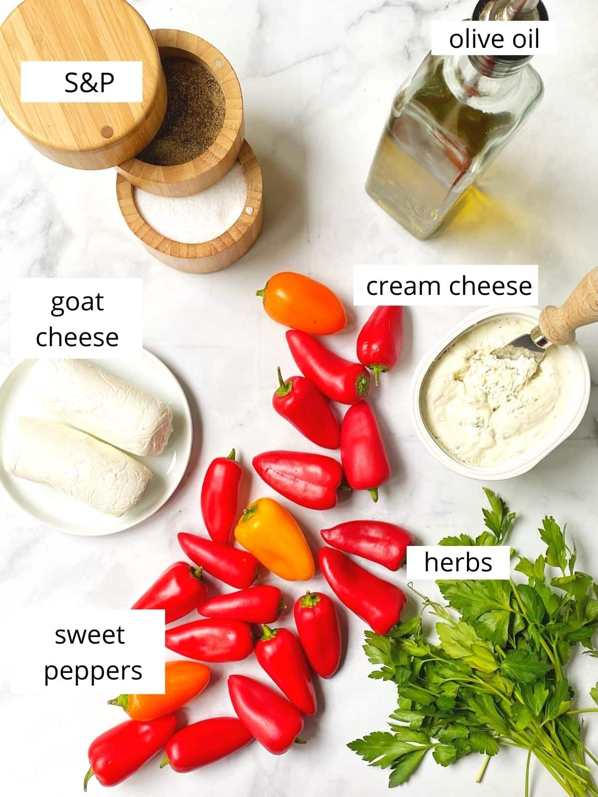 array of ingredients - peppers, goat cheese, cream cheese, herbs, oil, salt and pepper