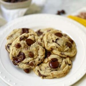 cookies layered on a white plate with a bowl of chocolate chips in the background