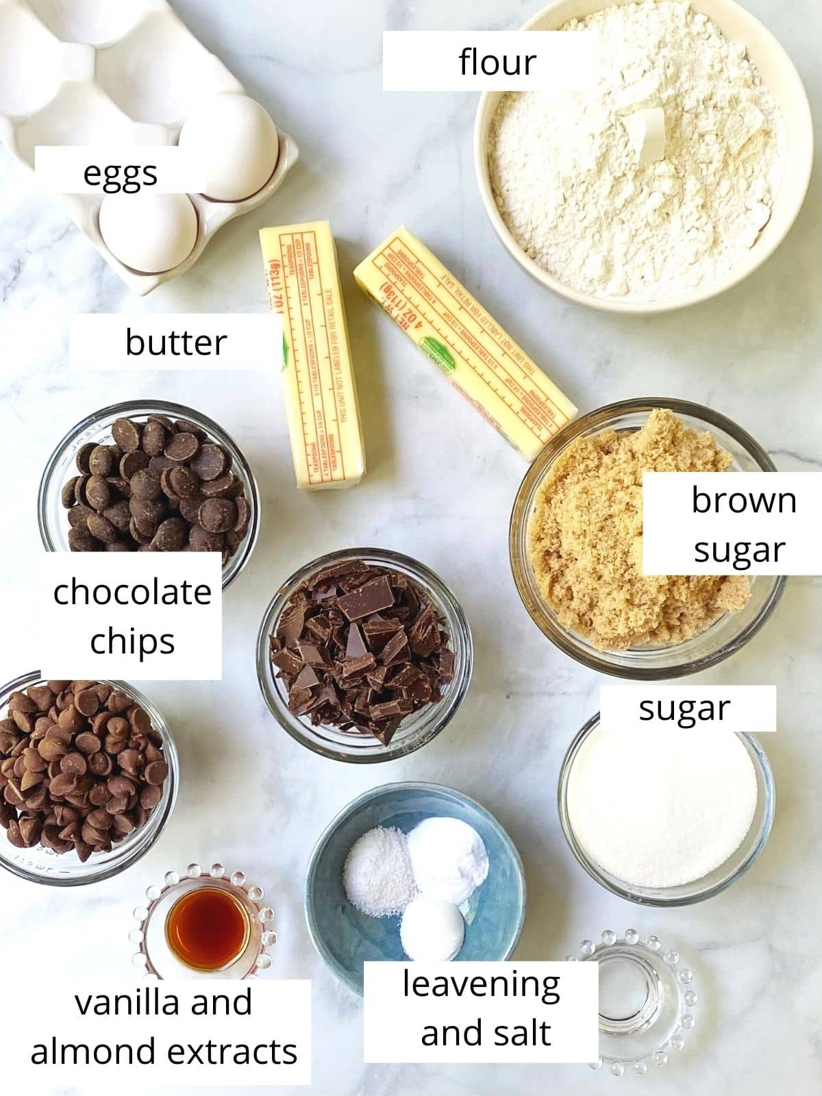 array of ingredients - eggs, butter, flour, sugar, brown sugar, leavening, salt, extracts, and chocolate chips