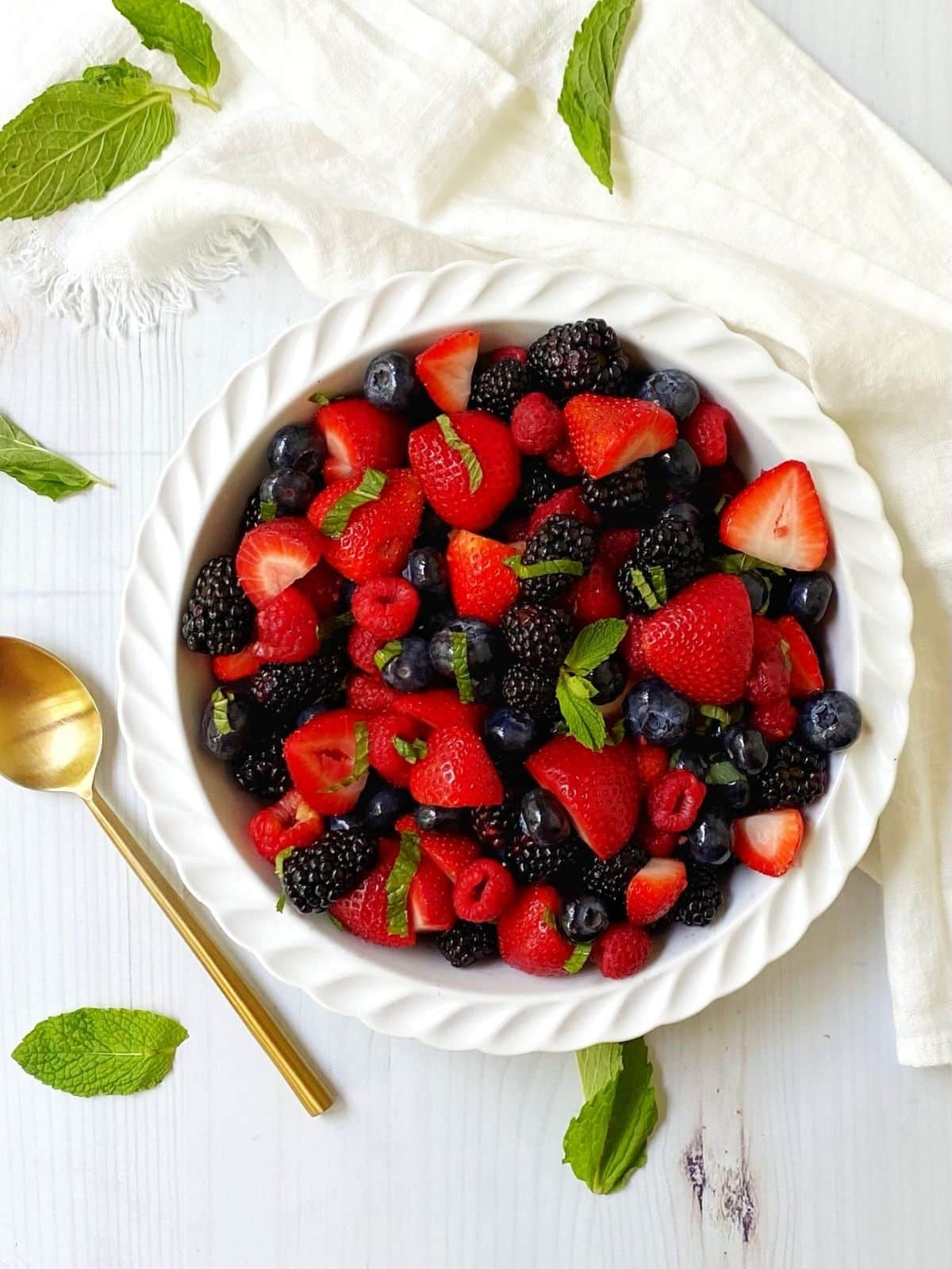 overhead shot of fruit salad in a white dish with serving spoon on the side