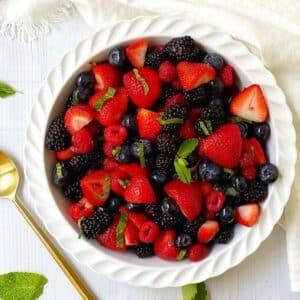 white dish of fruit salad garnished with fresh mint.